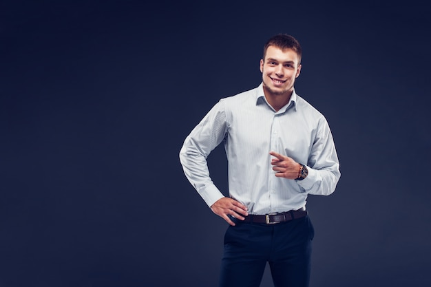Fashion young serious man in stripped shirt points finger, smiling and looking at camera on dark background.