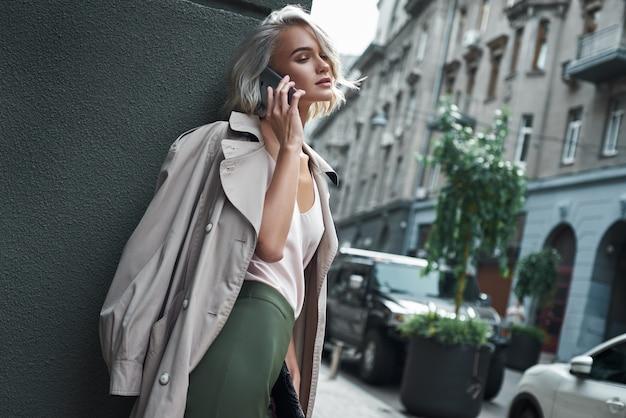 도시 거리에 서서 웃고 있는 친구와 스마트폰으로 이야기하는 세련된 젊은 여성