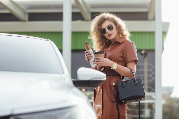 ガソリンスタンドの車の近くの駐車場でホットドッグを食べるファッションの若い女性
