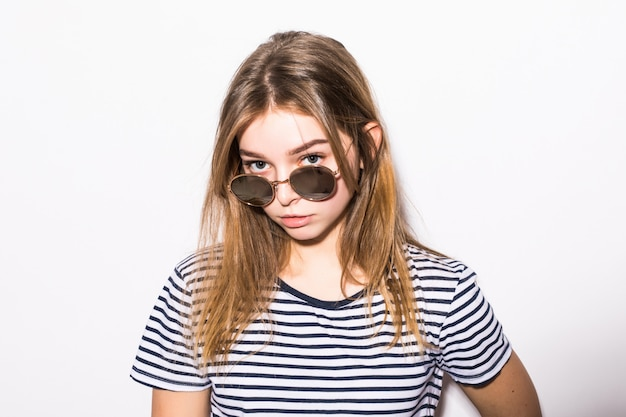 Fashion young woman hipster in sunglasses isolated on white wall