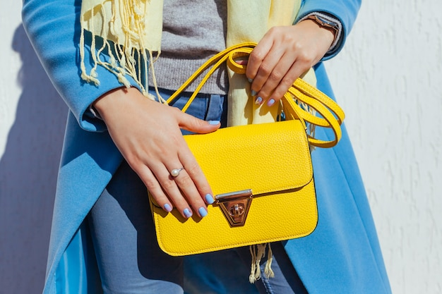 Fashion. young woman holding stylish handbag and wearing trendy blue coat. spring female clothes and accessories.