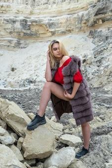 砂の岩の上でポーズをとって毛皮のコートで若い女性をファッション