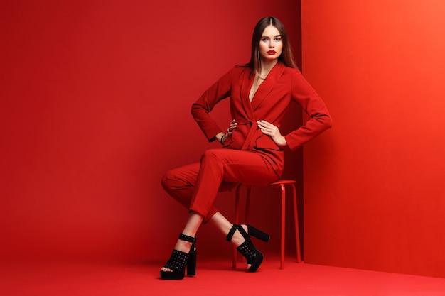 赤いスーツを着たファッションの若い女性。赤い背景。