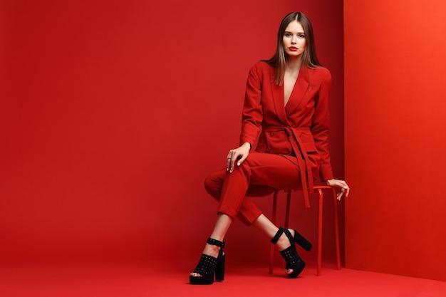 Молодая женщина моды в красном костюме