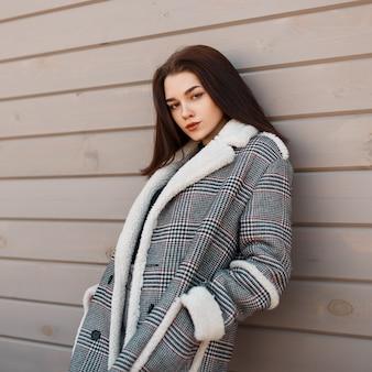 빈티지 코트와 세련된 착실히 보내다에서 패션 젊은 여자는 깔끔한 나무 배경을 의미합니다