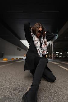街のアスファルトでポーズをとるブーツのジーンズのスタイリッシュな黒のコートで頭にシルクのエレガントなスカーフのサングラスでファッションの若い女性。現代のビジネスガールモデル。女性のための流行の服。レトロ。