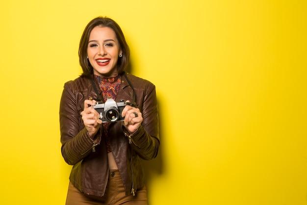 패션 젊은 여자가 노란색 벽에 오래 된 카메라로 사진을 만든다