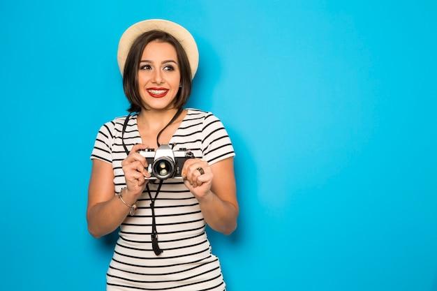 Молодая женщина моды делает фото со старой камерой