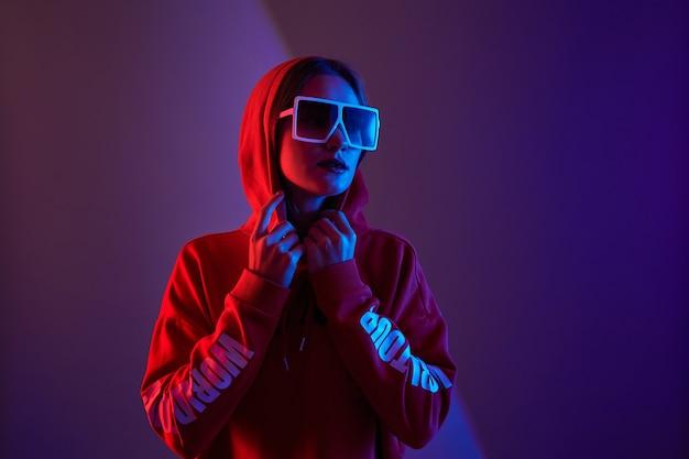 Мода молодой женщины модель носить толстовку с капюшоном и солнцезащитные очки в неоновом свете студии фоне.