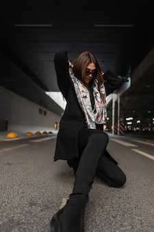 Fashion young woman in sunglasses in silk elegant scarf on head in stylish black coat in jeans in boots posing on the asphalt in the city. modern business girl model. trendy clothes for women. retro.