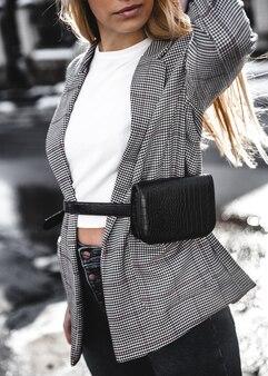 黒い帽子の市松模様のコートジャケットのハンドバッグを身に着けているファッションの若い女性
