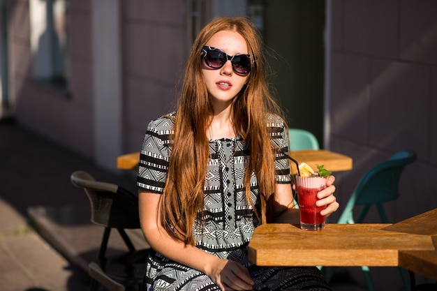 Moda giovane donna con i capelli lunghi e un sorriso incredibile, che tiene una gustosa limonata cocktail estivo dolce