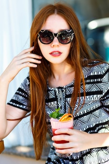 長い髪と素晴らしい笑顔のファッションの若い女性、おいしい甘い夏のカクテルレモネード、エレガントなドレスを保持している、メイクアップ、都市のカフェでリラックス。幸せな楽しい感情。