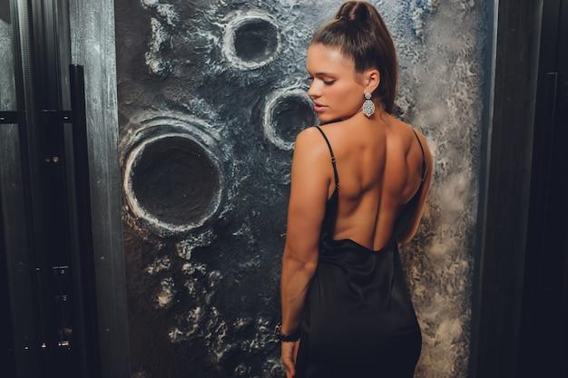 壁に美しいドレスを着てポーズをとるファッションの若い女性。