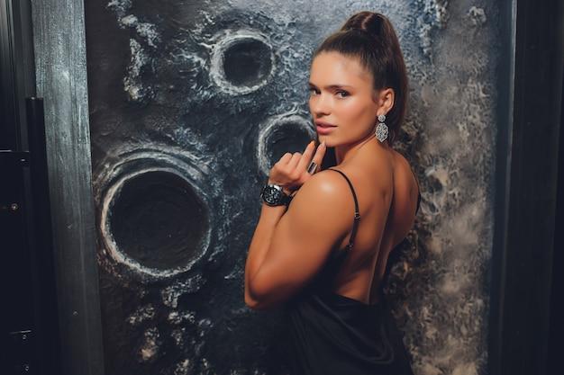 Молодые женщины моды представляя в красивом платье на стене.