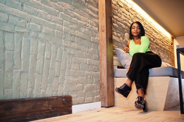 薄緑のトップと黒のズボンのポーズでファッショナブルなアフリカ系アメリカ人の女性。