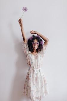 手を上げてポーズをとるファッショナブルなアフリカの女の子。家で楽しんでいるエレガントな黒人女性の肖像画。
