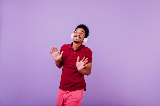 トレンディな赤い服装で見上げるファッショナブルなアフリカ人。ぶらぶらしているヘッドフォンの洗練された男
