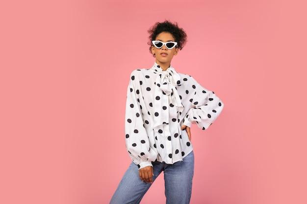 Модная африканская женщина в белой блузке и джинсах позирует на розовом фоне