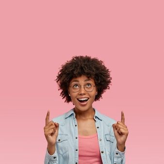 Fashionable afro american lady has curly dark hair, wears round glasses, indicates with both index fingers upwards, shows direction upstairs, glad with buying new apartment, isolated on pink wall