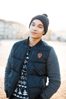 Fashionable american young man with a charming smile in a vintage stylish hat in a christmas knitted sweater with a white pattern in a winter jacket is stands outdoors in the city. happy guy.