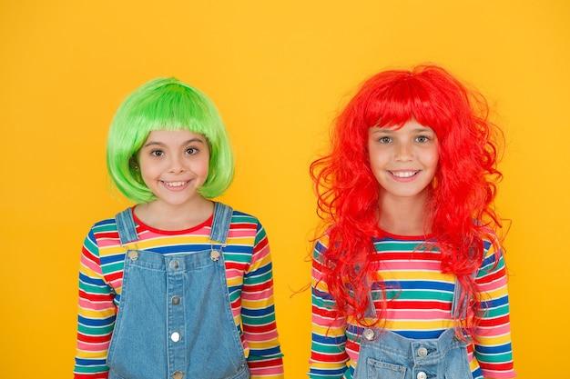 Модно и артистично. счастливые дети носят модные парики на желтом фоне. маленькие девочки улыбаются модным взглядом. fashioanble парикмахерская. мода и стиль.