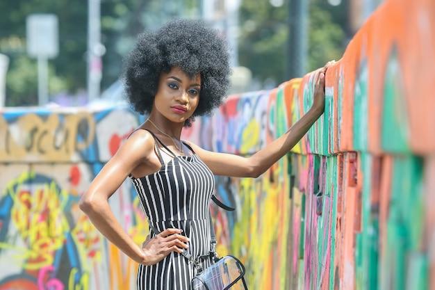 縞模様の服のポーズでファッショナブルで美しいアフリカの女の子