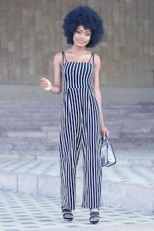 Модная и красивая африканская девушка в полосатой одежде позирует