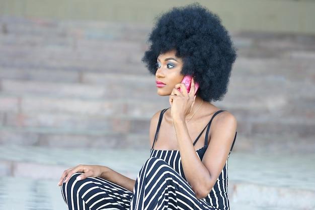 電話で話している縞模様の服を着たファッショナブルで美しいアフリカの女の子