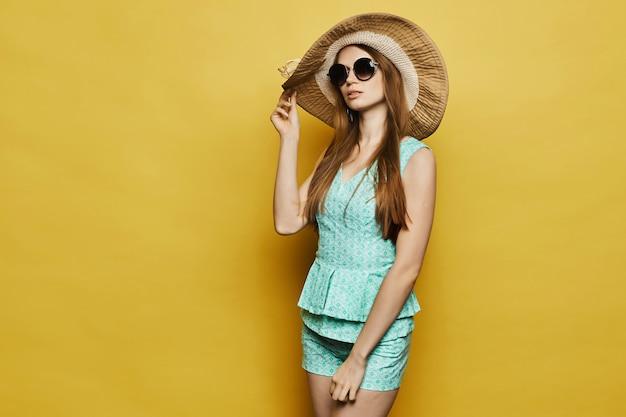 Модная и красивая модель-блондинка в стильных шортах, блузке и солнцезащитных очках поправляет шляпу и позирует. скопируйте место для вашего текста.