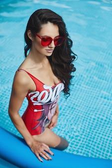 スタイリッシュな赤いビキニと魅力的なサングラスで完璧なセクシーなボディを持つファッショナブルで美しいブルネットモデルの女性が屋外のスイミングプールでポーズ