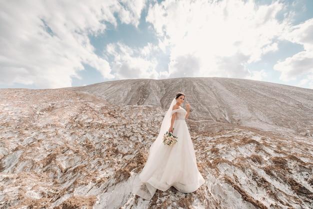 Модная и красивая пара, счастливая блондинка модель девушка со стильной прической, в белом кружевном платье и стильный красавец в модном костюме на соляной горе.