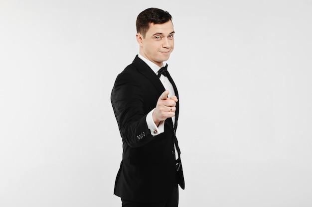 Модный и красивый молодой эмоциональный мужчина в белой рубашке и в стильном черном костюме с галстуком-бабочкой