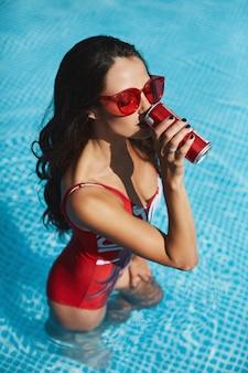 スタイリッシュな赤い水着で完璧なセクシーな姿と冷たい飲み物を飲みながらプールでトレンディな赤いサングラスをかけたファッショナブルで幸せなブルネットモデルの女性