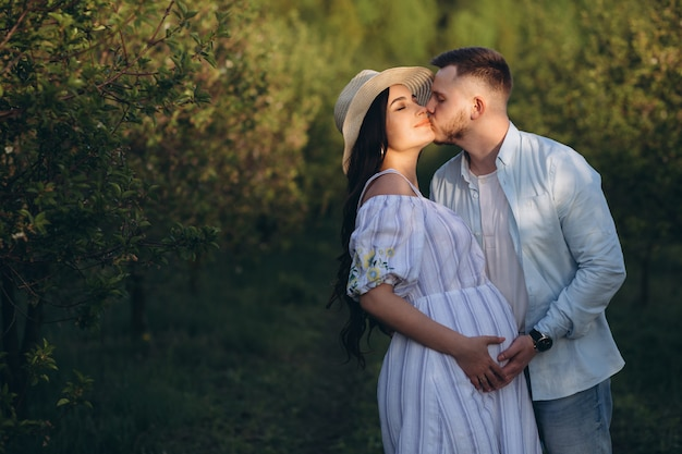 ファッショナブルでスタイリッシュな幸せな妊娠中の女性と彼女の夫は、夕日の庭でパステルホワイトとブルーのトーンを着てください。