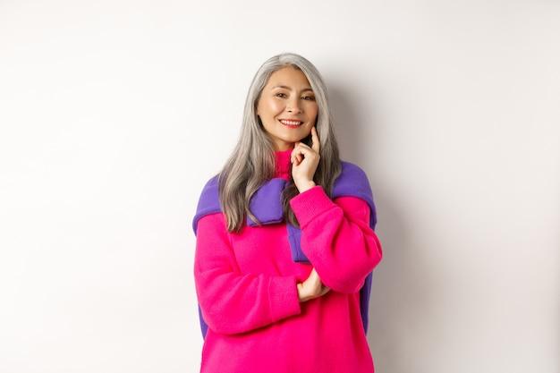 회색 머리를 한 세련된 아시아 중년 여성, 기쁘고 사려 깊은 미소를 지으며 생각을 갖고 흰색 배경 위에 서 있습니다.