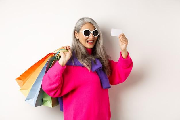 Модная азиатская старушка идет по магазинам, держа бумажные пакеты и пластиковую кредитную карту, в стильных солнцезащитных очках, стоя на белом.