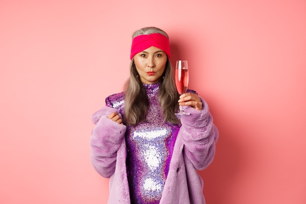 Fashionable asian senior female model raising glass of champagne, wearing trendy glitter dress and faux fur and looking at camera, congratulating with holiday, pink background