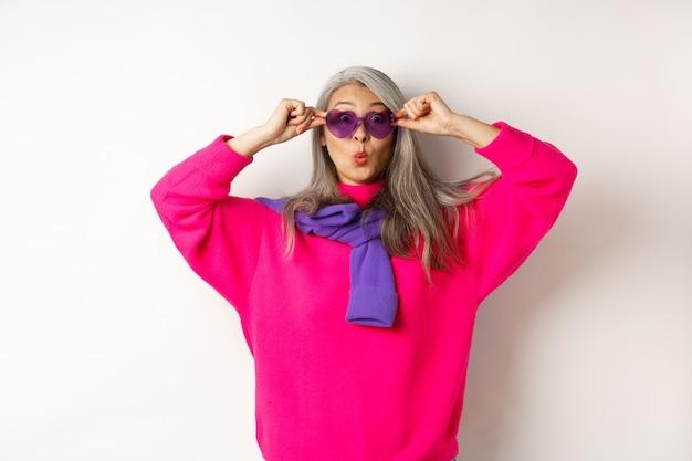 Модная азиатская старшая женщина в солнцезащитных очках и стильном розовом свитере сморщивает губы, поднимает брови и удивленно смотрит в камеру, белый фон