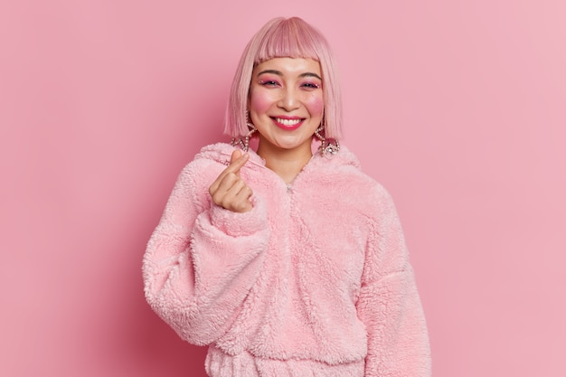 Fashionable asian woman with bright makeup makes mini heart gesture korean like sign smiles pleasantly has pink hair and fur coat poses indoor dresses for disco party. body language concept.