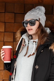 Fashionable attractive young hipster woman in knitted hat in sunglasses with a black jacket with a fur hood in a hoodie posing near a wooden wall outdoors. beautiful girl drinks hot coffee.