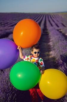 점이 있는 화려한 옷을 입은 세련된 소년은 여름에 꽃이 만발한 라벤더 밭에서 풍선을 들고 있다