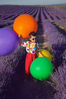 점이 있는 화려한 옷을 입은 세련된 소년은 꽃이 만발한 라벤더에 풍선을 들고 있습니다