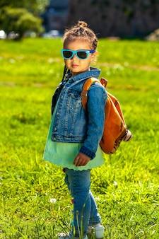 サングラスでファッショナブルな女の赤ちゃん。夏の公園でデニムスーツを着て