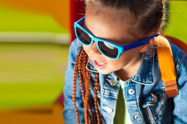 ジーンズのスーツのサングラスでファッショナブルな女の赤ちゃん