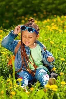 自然の草のサングラスに座っているファッショナブルな女の赤ちゃん