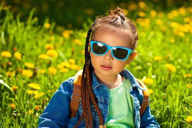 Модная девочка, сидящая в солнечных очках в траве на природе