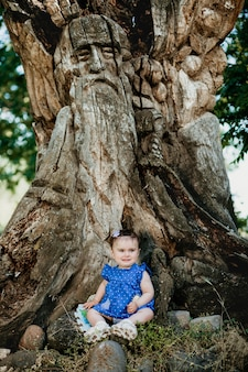 Fashionable baby with blue dress sitting at old giant tree and smiling