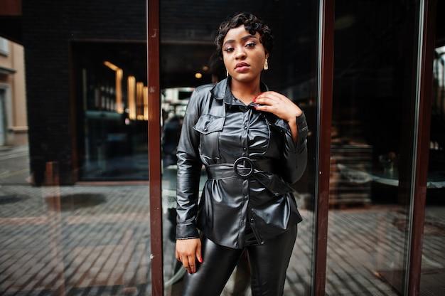 通りで黒い革のジャケットとズボンでポーズをとるファッショナブルな美しいアフリカ系アメリカ人の女性。鼻のイヤリング。