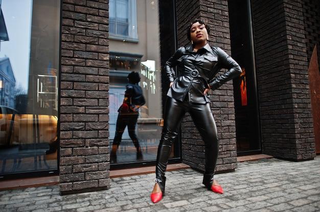 通りで黒い革のジャケットとズボンでポーズをとるファッショナブルな美しいアフリカ系アメリカ人の女性。 Premium写真